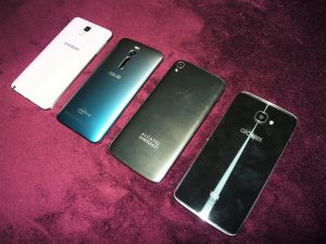 De gauche à droite vus de dos : Samsung Galaxy Note 3, Asus Zenphone 2, Alcatel Idol 3, Alcatel Idol 4S